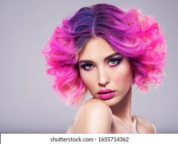 Portrait of beautiful young woman with bright pink makeup. Beautiful blonde with bright pink lipstick on her lips. Pretty girl with vivid hair. Blonde with brightly colored hair. Bright eye makeup.