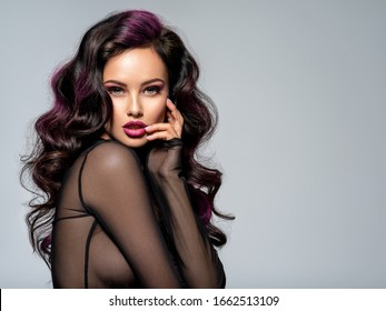 Portrait of beautiful young woman with bright maroon makeup. Beautiful brunette with bright cherry lipstick on her lips. Pretty girl with long black hair. Brunette with brightly colored hair