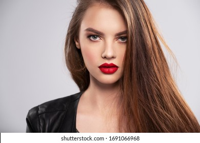Portrait of beautiful young woman with bright makeup. Beautiful brunette with bright red lipstick on her lips. Pretty girl with long brown hair. Brunette dressed in a black leather jacket. Sexy girl