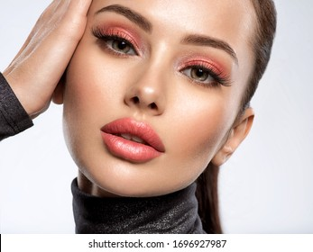 Portrait of beautiful young woman with bright pink makeup. Beautiful brunette with bright orange lipstick on her lips. Pretty girl with beautiful eyes.