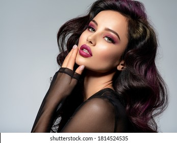 Portrait of beautiful young woman with bright maroon makeup. Beautiful brunette with bright cherry lipstick on her lips. Pretty girl with long black hair. Brunette with brightly colored hair.