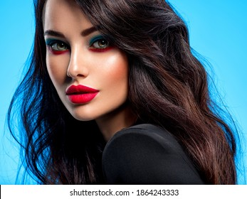 Portrait of beautiful young woman with bright blue makeup. Beautiful brunette with bright red lipstick on her lips. Pretty girl with long black hair. Closeup face of brunette woman.