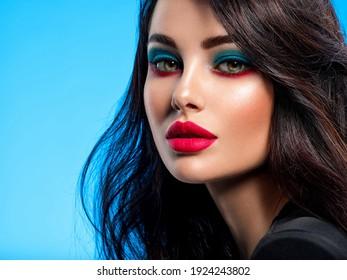 Portrait von schönen jungen Frau mit hellblauem Make-up. Schöne Brunette mit hellrotem Lippenstift auf ihren Lippen. Hübsches Mädchen mit langen schwarzen Haaren. Nahaufnahme von Gesicht der Brunette Frau.