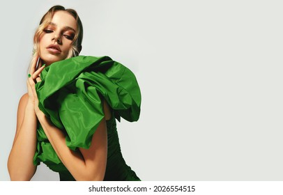 Portrait of a beautiful young woman with bright makeup and in a bright green dress. Advertising of fashionable clothes, decorative cosmetics advertising concept. Fashionable dress.