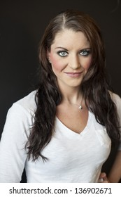 Portrait of a beautiful young woman with brown hair and blue eyes.