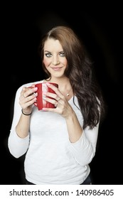 Portrait of a beautiful young woman with brown hair and blue eyes. She is on a black background and drinking coffee from a red cup.