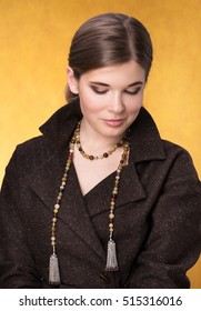 Portrait of beautiful young woman in a brown cloak with beads on the neck. The gaze is directed to the bottom, with a slight smile. Neutral Golden background