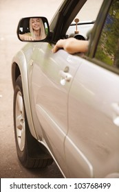 Portrait of beautiful young woman in car is reflected in the mirror.