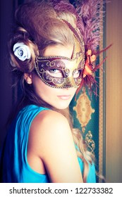 Portrait of a beautiful young woman in a carnival mask. Vintage style.