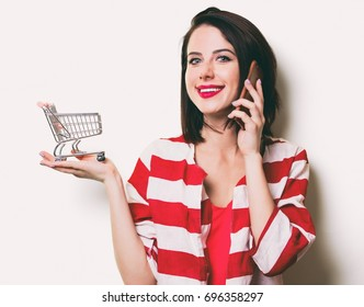 portrait of the beautiful young woman with cart for shopping and mobile phone