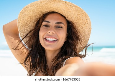Portrait of beautiful young woman in casual wearing straw hat at seaside.Cheerful young woman smiling at beach during summer vacation. Happy girl with black hair and freckles enjoying the sun. - Shutterstock ID 1667783035