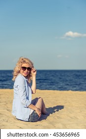 Portrait of beautiful young woman in casual clothes and sun glasses looking at camera and smiling while sitting on the sunny beach