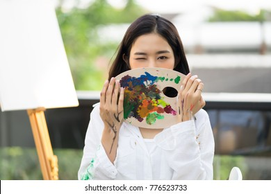 Portrait of a beautiful young woman in causal clothes covering her mouth hand holding art palette, Painting Concept,Lifestyle concept.