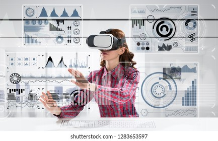 Portrait of beautiful and young woman in checkered shirt using virtual reality goggles and interracting with digital media interface while sitting inside bright office building.