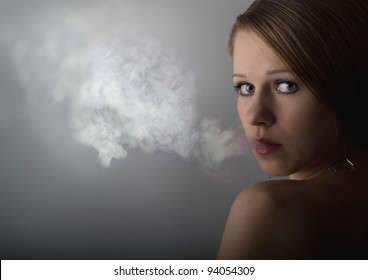 portrait of a beautiful young woman with cigarette smoke on a dark gray background