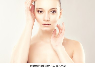 Portrait of Beautiful Young Woman with Clean Skin and Nude MakeUp. Girl Touching Own Face. Youth and Skin Care Concept. Cosmetology, Beauty and Spa.