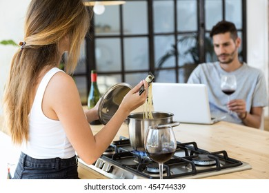 Portrait of beautiful young woman cooking and young man using his laptop.
