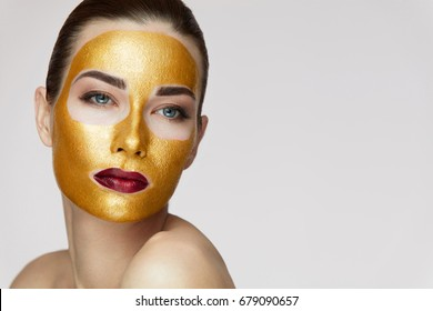 Portrait Of Beautiful Young Woman With Cosmetic Golden Mask On Beauty Face.