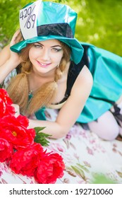 Portrait of a beautiful young woman in a costume of the Mad Hatter in nature. Girl posing with a bouquet of red peonies