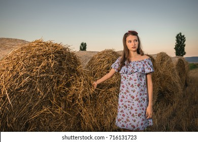 Portrait of beautiful young woman in countryside, romanian girl in haystacks