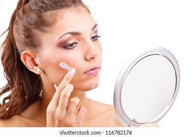 Portrait of beautiful young woman with cream on her face