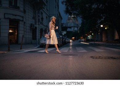 Portrait of a beautiful young woman crossing the street