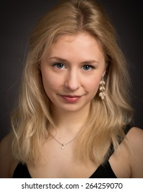 Portrait of a beautiful young woman with curly long blond hair, blue eyes wearing a purple top isolated against a dark grey background.