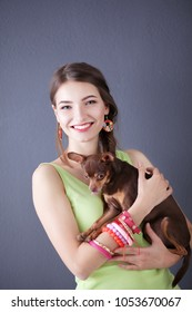 portrait of the beautiful young woman with dog on the grey background