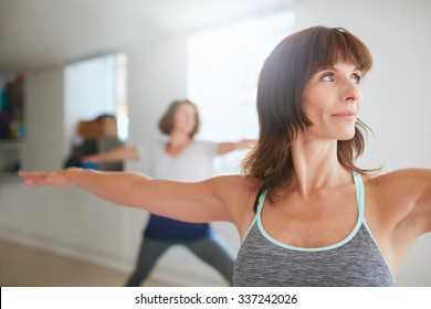 Portrait of beautiful young woman doing the warrior pose during yoga class. Yoga instructor performing Virabhadrasana position in gym.