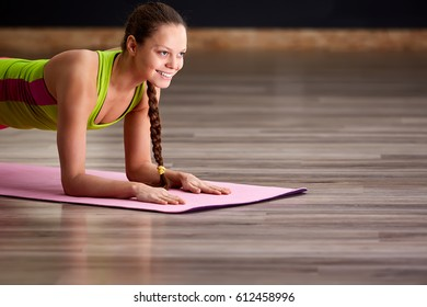 Portrait of beautiful young woman doing yoga exercise - smiling woman on the yoga mat