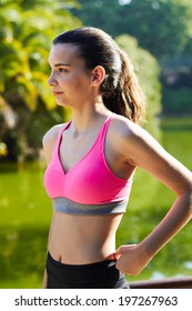 Portrait of beautiful young woman dressed in sportswear taking a break after run, charming fit girl resting after workout in sunny park