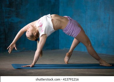 Portrait of beautiful young woman dressed in shorts and white top enjoying yoga indoors. Yogi girl working out in grunge interior with blue wall. Camatkarasana, Wild Thing or Flip-the-Dog posture