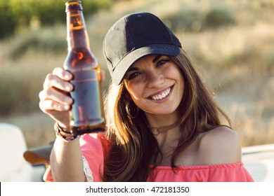 Portrait of beautiful young woman drinking beer and enjoying summer day.
