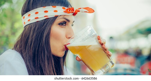 Portrait of beautiful young woman drinking beer and enjoying summer day