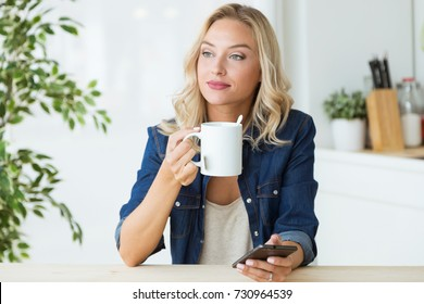 Portrait of beautiful young woman drinking coffee at home.