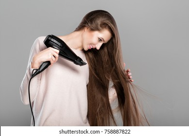 portrait of beautiful young woman drying her long hair with dryer over gray background