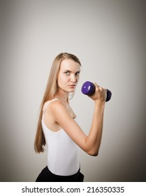 Portrait of beautiful young woman with dumbbell. Healthy lifestyle concept. Young woman doing something.