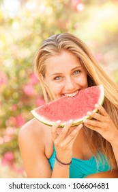 Portrait of a beautiful young woman eating watermelon