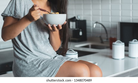 Portrait of beautiful young woman eating bowl of cereal and fruit at home in kitchen.