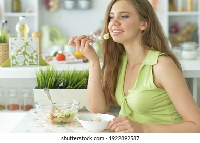 Portrait of beautiful young woman eating salad in kitchen