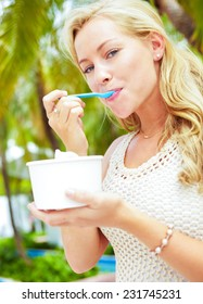 Portrait of beautiful young woman eating frozen yogurt with strawberries in park