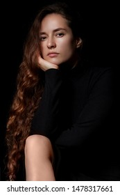 Portrait of a beautiful young woman with elegant long red shiny hair , hairstyle.In black elegant dress.