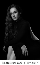 Portrait of a beautiful young woman with elegant long red shiny hair , hairstyle.In black elegant dress.Black and white