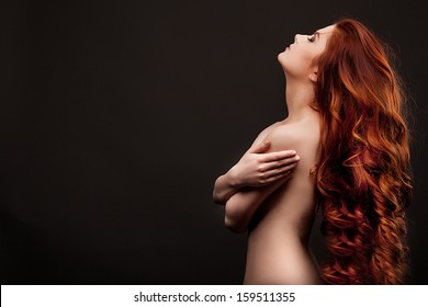 portrait of a beautiful young woman with elegant long red shiny hair , hairstyle
