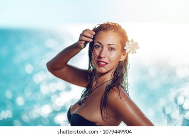 Portrait of a beautiful young woman enjoying on the beach. She is smiling and looking at camera.