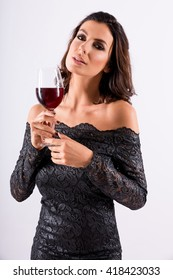 Portrait of a beautiful young woman enjoying a glass of wine while wearing a nice black dress in the studio.