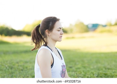 Portrait of beautiful young woman enjoying yoga, relaxing and breathing fresh air in green summer park. Calm and dreaming copy space concept