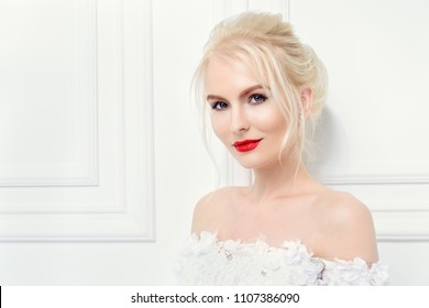 Portrait of a beautiful young woman in evening or wedding white dress. Evening hairstyle and makeup.