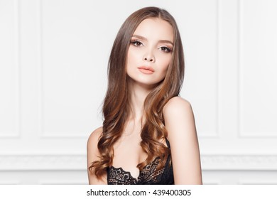 portrait of beautiful young woman with evening make-up and hairstyle against white wall