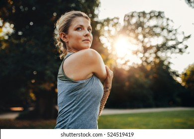 Portrait of beautiful young woman exercising in the park. Caucasian female fitness model working out in the morning.